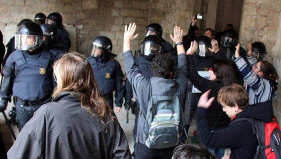 Los mossos dialogando con un grupo de jóvenes en el claustro de la universidad.