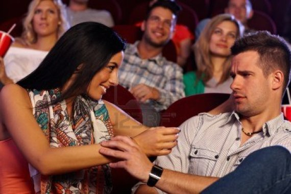 15642335-pretty-young-woman-molesting-young-man-at-movie-theater